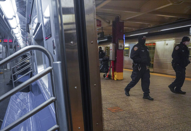 Police patrol the A line subway train bound to Inwood, after NYPD deployed an additional 500 officers into the subway system following deadly attacks, Saturday Feb. 13, 2021, in New York. Authorities say an unidentified man could be responsible for four separate stabbing attacks in the New York City subways that have left two people dead. New York police say the assaults happened between Friday morning and early Saturday. (AP Photo/Bebeto Matthews)