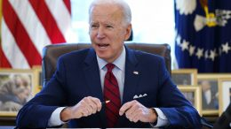 FILE - In this Jan. 28, 2021 file photo, President Joe Biden signs a series of executive orders in the Oval Office of the White House in Washington. Biden campaigned on raising the national minimum wage to $15 per hour and attached a proposal doing just that to the $1.9 trillion coronavirus pandemic relief bill. (AP Photo/Evan Vucci)