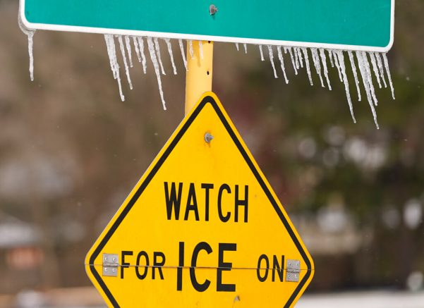 Icicles hang on a watch for ice on bridge road sign Monday, Feb. 15, 2021 in Houston. A winter storm making its way from the southern Plains to the Northeast is affecting air travel. (Melissa Phillip/Houston Chronicle via AP)