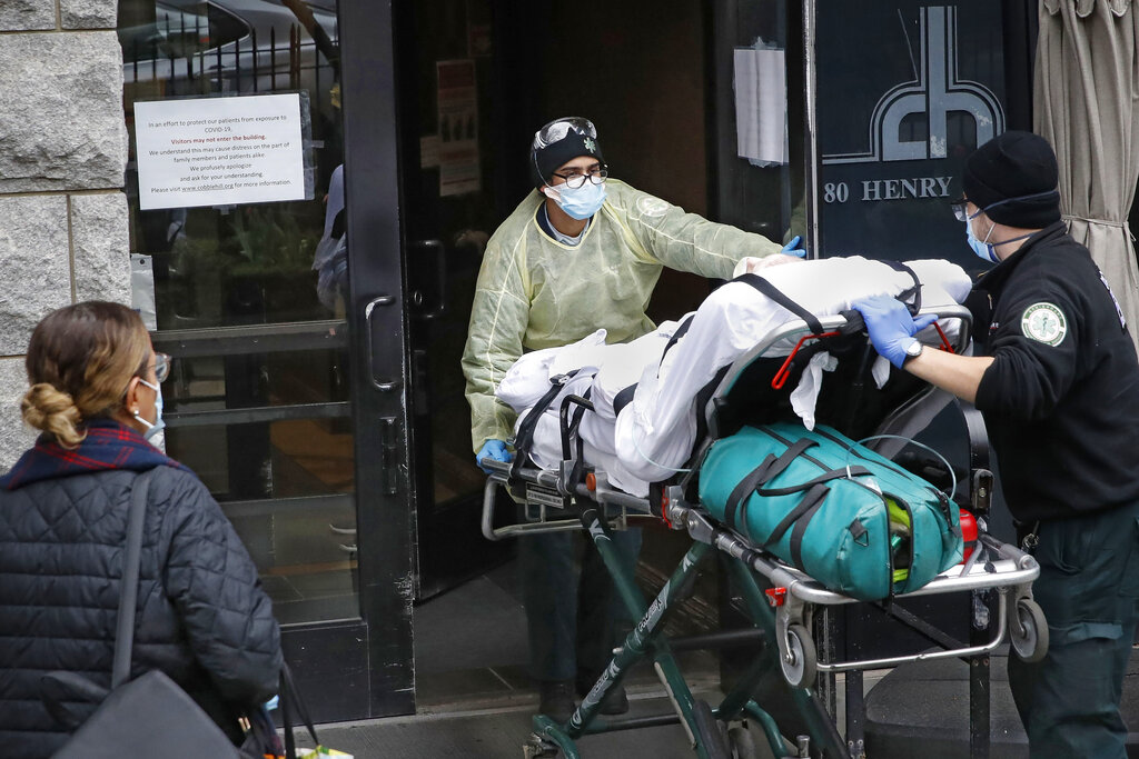 FILE- In this April 17, 2020, file photo, a patient is wheeled into Cobble Hill Health Center by emergency medical workers, in the Brooklyn borough of New York. Under fire over his management of the coronavirus' lethal path through New York's nursing homes, New York Gov. Andrew Cuomo insisted Monday, Feb.15, 2021, the state didn't cover up deaths but acknowledged that officials should have moved faster to release some information sought by lawmakers, the public and the press. (AP Photo/John Minchillo, File)