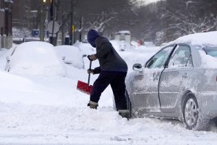 A motorist digs a path for his car Tuesday, Feb. 16, 2021, to enter an unplowed side street in the Bronzville neighborhood of the South Side of Chicago. A winter storm that blanketed the Chicago area overnight with up to 18.5 inches of snow. (AP Photo/Charles Rex Arbogast)