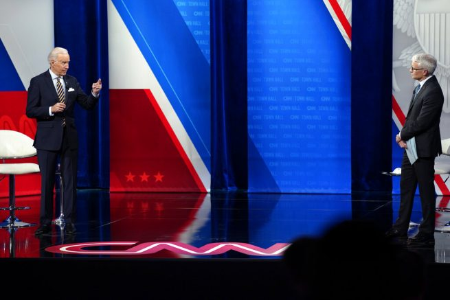 President Joe Biden speaks as Anderson Cooper listens during a televised town hall event at Pabst Theater, Tuesday, Feb. 16, 2021, in Milwaukee. (AP Photo/Evan Vucci)