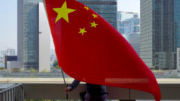"A pro-China supporter holds a Chinese national flags outside High Court in Hong Kong Thursday, Feb. 18, 2021. Prominent Hong Kong democracy advocate and newspaper founder Jimmy Lai is back in court for another attempt to apply for bail before his trial in April, on the charge of ""collusion with foreign forces,"" a new crime in Hong Kong invented by the National Security Law that Beijing imposed last year. (AP Photo/Vincent Yu)"