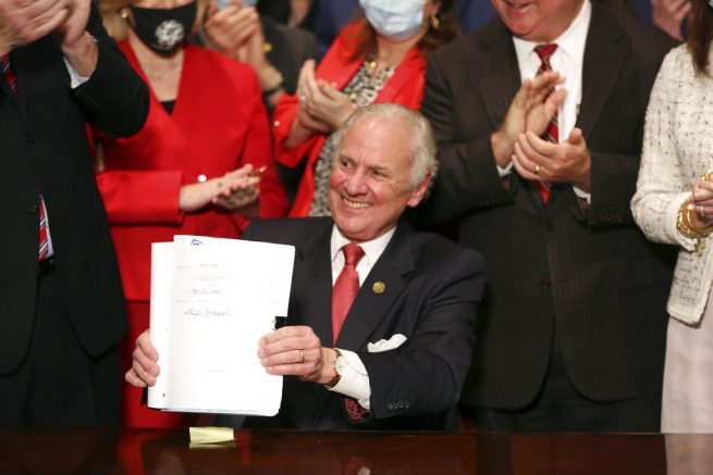 "South Carolina Gov. Henry McMaster holds up a bill banning almost all abortions in the state after he signed it into law on Thursday, Feb. 18, 2021, in Columbia, S.C. On the same day, Planned Parenthood filed a federal lawsuit to stop the measure from going into effect.  The state House approved the ""South Carolina Fetal Heartbeat and Protection from Abortion Act"" on a 79-35 vote Wednesday and gave it a final procedural vote Thursday before sending it to McMaster.  (AP Photo/Jeffrey Collins)"