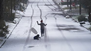 Children play with a sled as snow begins to accumulate, Thursday, Feb. 18, 2021, in San Antonio. Snow, ice and sub-freezing weather continue to wreak havoc on the state's power grid and utilities. (AP Photo/Eric Gay)