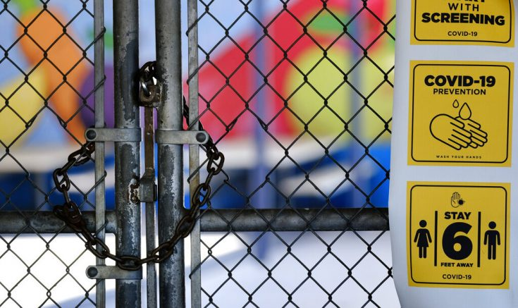 FILE - In this July 13, 2020, file photo, a gate is locked at the closed Ranchito Elementary School in the San Fernando Valley section of Los Angeles. After weeks of tense negotiations, California legislators agreed Thursday, Feb. 18, 2021, on a $6.5 billion proposal aimed at getting students back in classrooms this spring following months of closures because of the pandemic. (AP Photo/Richard Vogel, File)