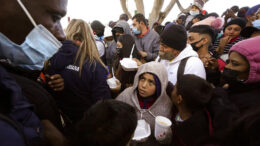 Asylum seekers receive food as they wait for news of policy changes at the border, Friday, Feb. 19, 2021, in Tijuana, Mexico. After waiting months and sometimes years in Mexico, people seeking asylum in the United States are being allowed into the country starting Friday as they wait for courts to decide on their cases, unwinding one of the Trump administration's signature immigration policies that President Joe Biden vowed to end. (AP Photo/Gregory Bull)