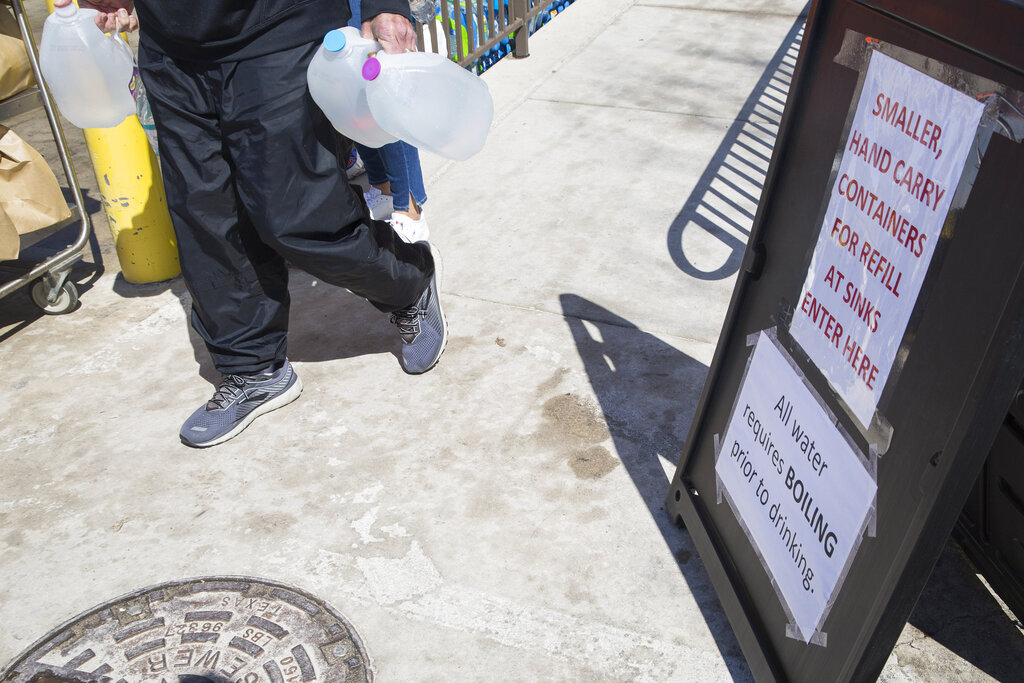 A man walks with jugs of water past a sign reminding residents their water needs to be boiled as people fill up containers at the water station at the New Braunfels Civic/Convention Center in New Braunfels, Texas, Friday, Feb. 19, 2021. The water stations were set up by New Braunfels Utilities and the city of New Braunfels for area residents without water in the wake of outages throughout the city due to unprecedented winter weather events. (Mikala Compton/Herald-Zeitung via AP)