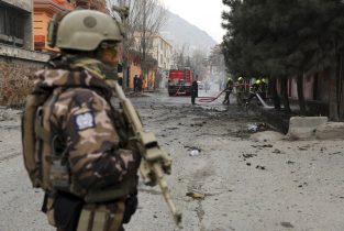 A soldier stands guard as firefighters work at the site of a bomb attack in Kabul, Afghanistan, Saturday, Feb. 20, 2021. Three separate explosions in the capital Kabul on Saturday killed and wounded numerous people an Afghan official said. (AP Photo/Rahmat Gul)