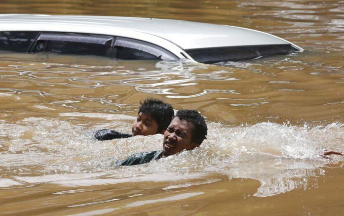 People swim through a flooded neighborhood following heavy rains in Jakarta, Indonesia, Saturday, Feb. 20, 2021. Heavy downpours combined with poor city sewage planning often causes heavy flooding in parts of greater Jakarta. (AP Photo/Tatan Syuflana)