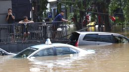 People stand above at an office yard flooded following heavy rains, Saturday, Feb. 20, 2021 in Jakarta, Indonesia. Heavy downpours combined with poor city sewage planning often causes heavy flooding in parts of greater Jakarta. (AP Photo/Tatan Syuflana)