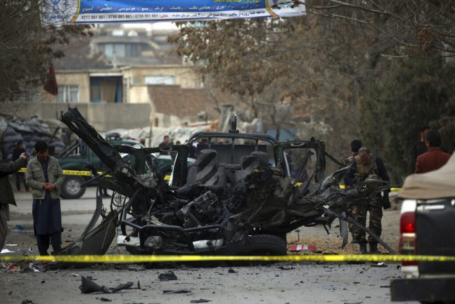 Afghan security personnel remove a damaged vehicle from the site of a bomb attack in Kabul, Afghanistan, Saturday, Feb. 20, 2021. Three separate explosions in the capital Kabul on Saturday killed and wounded multiple people, an Afghan official said. (AP Photo)