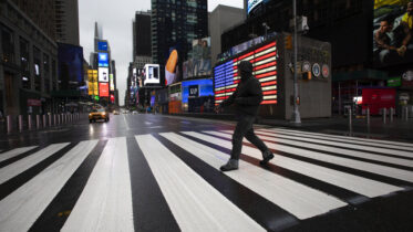 A man crosses the street in a nearly empty Times Square, which is usually very crowded on a weekday morning in New York, March 23, 2020. (AP Photo/Mark Lennihan)