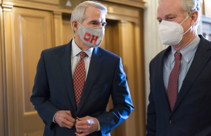 Sen. Rob Portman, R-Ohio, left, and Sen. Chris Van Hollen, D-Md., walk to the chamber as senators arrive to vote on President Joe Biden's nominee for United Nation's ambassador, Linda Thomas-Greenfield, at the Capitol in Washington, Tuesday, Feb. 23, 2021. (AP Photo/J. Scott Applewhite)