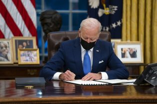 FILE - In this Feb. 2, 2021, file photo, Joe Biden signs an executive order, in the Oval Office of the White House, in Washington. Biden is signing an executive order Wednesday to review the United States' supply chains for large capacity batteries, pharmaceuticals, critical minerals and semiconductors. (AP Photo/Evan Vucci, File)