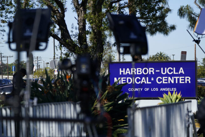 The sign at the front entrance of Harbor-UCLA Medical Center is seen through television cameras and lights, Wednesday, Feb. 24, 2021, in Torrance, Calif. Golfer Tiger Woods was hospitalized and underwent surgery at Harbor-UCLA Medical Center following a car accident on Tuesday. (AP Photo/Ashley Landis)