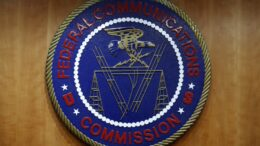 FILE - In this Dec. 14, 2017, file photo, the seal of the Federal Communications Commission (FCC) is seen before an FCC meeting to vote on net neutrality in Washington. U.S. communications regulators on Thursday, May 9, 2019, rejected a Chinese telecom company's application to provide service in the U.S. due to national-security risks amid an escalation in tensions between the two countries. The FCCC on Thursday voted unanimously, 5-0 across party lines, to reject China Mobile International USA Inc.'s long-ago filed application. (AP Photo/Jacquelyn Martin, File)