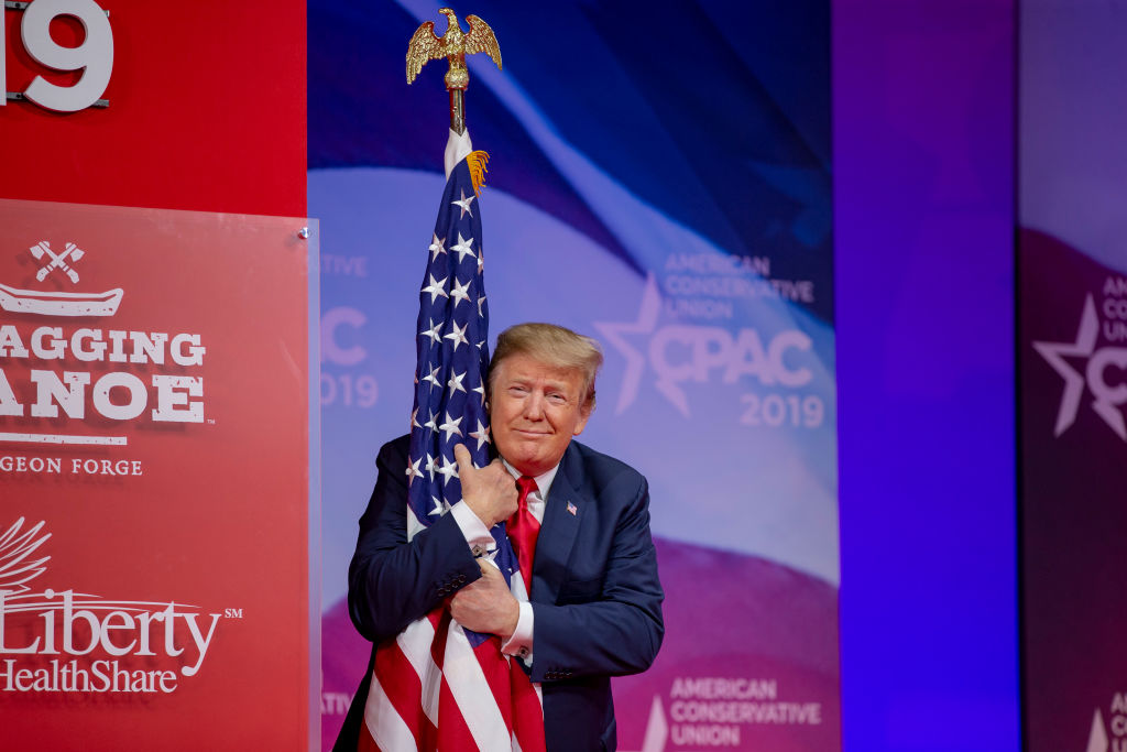 NATIONAL HARBOR, MD - MARCH 02: (AFP OUT) U.S. President Donald Trump hugs the U.S. flag during CPAC 2019 on March 02, 2019 in National Harbor, Maryland. The American Conservative Union hosts the annual Conservative Political Action Conference to discuss conservative agenda. (Photo by Tasos Katopodis/Getty Images)