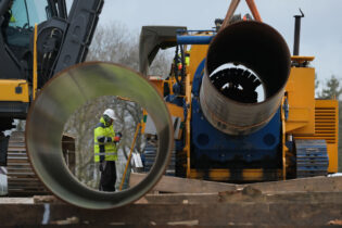 DAMEROW, GERMANY - MARCH 26: A worker stands next to a machine that is bending sections of pipe to fit the construction terrain at a pipe depot during construction of the Eugal gas pipeline on March 26, 2019 near Damerow, Germany. The Eugal gas pipeline will transport natural gas arriving from Russia through the Nord Stream 2 pipeline 480km across eastern Germany, from Lubmin on the Baltic Sea to the Czech border. (Photo by Sean Gallup/Getty Images)