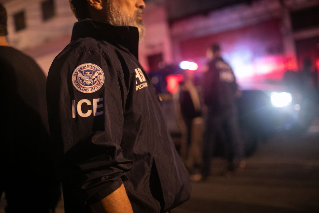 An ICE agent with U.S. Homeland Security Investigations (HSI), watches as Guatemalan police investigate the scene after detaining a suspected human trafficker on May 29, 2019 in Guatemala City. Homeland Security agents accompanied Guatemalan police on an early morning raid, the first since Acting U.S. Homeland Security Secretary Kevin McAleenan signed an agreement with his Guatemalan counterparts, increasing cooperation on human and drug smuggling. McAleenan is on a four-day trip to Guatemala. (Photo by John Moore/Getty Images)