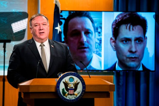 Michael Spavor, a Canadian businessman and Michael Kovrig, right, a former Canadian diplomat, detained in China since December 2018, are shown on a video monitor as US Secretary of State Mike Pompeo, speaks during a news conference at the State Department, Wednesday, July 1, 2020, in Washington. (Photo by Manuel Balce CENATA / POOL / AFP) (Photo by MANUEL BALCE CENATA/POOL/AFP via Getty Images)