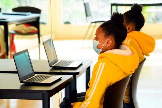 Children attend online classes at a learning hub inside the Crenshaw Family YMCA during the Covid-19 pandemic on February 17, 2021 in Los Angeles, California. - While many area schools remain closed for in-person classes, the learning hub program provides structured distance education resources including free WiFi, electricity, staff support, academic tutoring, and recreation activities to provide a safe environment to support low income and minority communities. (Photo by Patrick T. FALLON / AFP) (Photo by PATRICK T. FALLON/AFP via Getty Images)
