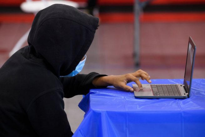 A child attends an online class at a learning hub inside the Crenshaw Family YMCA during the Covid-19 pandemic on February 17, 2021 in Los Angeles, California. - While many area schools remain closed for in-person classes, the learning hub program provides structured distance education resources including free WiFi, electricity, staff support, academic tutoring, and recreation activities to provide a safe environment to support low income and minority communities. (Photo by Patrick T. FALLON / AFP) (Photo by PATRICK T. FALLON/AFP via Getty Images)
