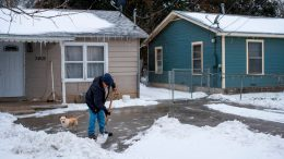 TOPSHOT - A Waco, Texas, resident clears snow from his driveway alongside his dog on February 17, 2021 as severe winter weather conditions over the last few days has forced road closures and power outages over the state. - Millions of people were still without power on February 17 in Texas, the oil and gas capital of the United States, and facing water shortages as an unusual winter storm pummeled the southeastern part of country. The National Weather Service (NWS) issued a winter storm warning for a swathe of the country ranging from east Texas to the East Coast state of Maryland. (Photo by Matthew Busch / AFP) (Photo by MATTHEW BUSCH/AFP via Getty Images)