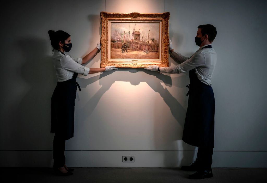 """Two employees put on display a painting titled """"Scene de rue a Montmartre"""" (Impasse des deux freres et le moulin à Poivre), 1887 by Dutch painter Vincent Van Gogh, at the Sotheby's auction house in Paris on February 24, 2021. - The painting will be auctionned on March 25, 2021 at the Sotheby's auction house in Paris. (Photo by STEPHANE DE SAKUTIN / AFP) / RESTRICTED TO EDITORIAL USE - MANDATORY MENTION OF THE ARTIST UPON PUBLICATION - TO ILLUSTRATE THE EVENT AS SPECIFIED IN THE CAPTION (Photo by STEPHANE DE SAKUTIN/AFP via Getty Images)"""