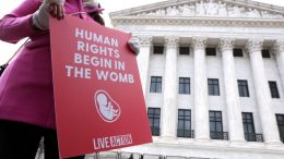 WASHINGTON, DC - JANUARY 29: A pro-life activist holds a sign outside the U.S. Supreme Court during the 48th annual March for Life January 29, 2021 in Washington, DC. Due to the COVID-19 pandemic, a much smaller group of activists participated in the annual march that marked the 1973 Roe v. Wade ruling by the U.S. Supreme Court that had legalized abortion. (Photo by Alex Wong/Getty Images)