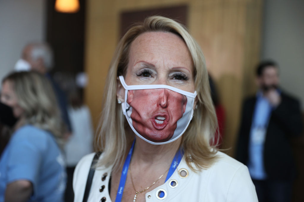 ORLANDO, FLORIDA - FEBRUARY 26: A visitor (who didn't want to provide her name) wears a face mask with a picture of former President Donald Trump on it during the Conservative Political Action Conference held in the Hyatt Regency on February 26, 2021 in Orlando, Florida. Begun in 1974, CPAC brings together conservative organizations, activists, and world leaders to discuss issues important to them. (Photo by Joe Raedle/Getty Images)