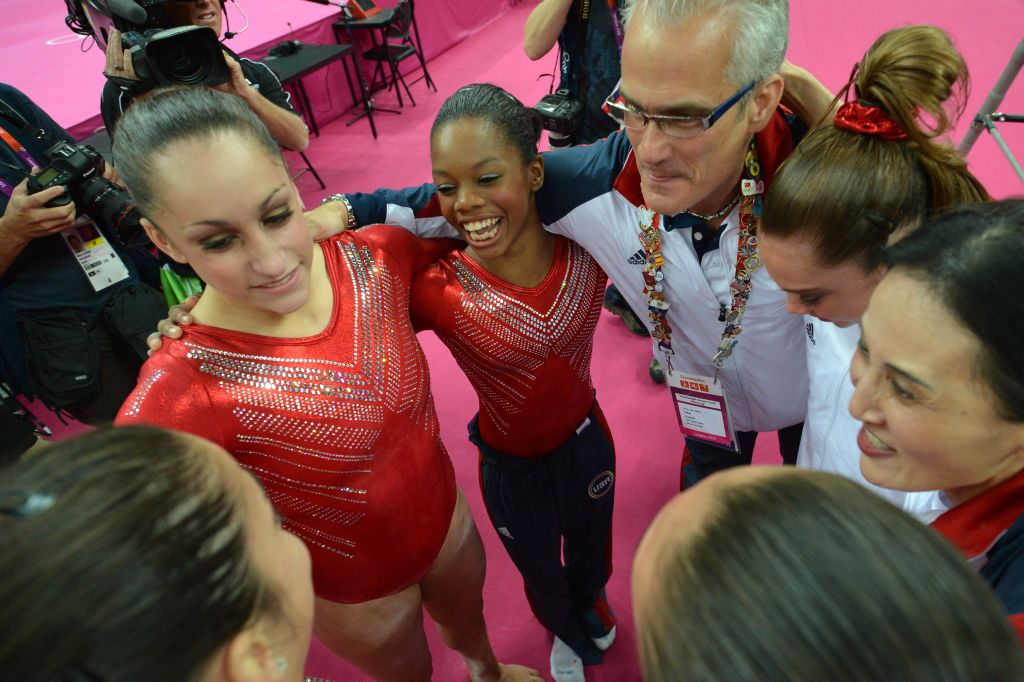 US gymnasts Gabrielle Douglas (C), Mckayla Maroney (2D-R), Alexandra Raisman (R), coaches Jenny Zhang (R) and John Geddert (3D-R) celebrate winning gold in the women's team of the artistic gymnastics event of the London Olympic Games on July 31, 2012 at the 02 North Greenwich Arena in London. Team US won gold, Team Russia took silver and Team Romania got bronze. AFP PHOTO / BEN STANSALL / AFP PHOTO / - (Photo credit should read -/AFP via Getty Images)