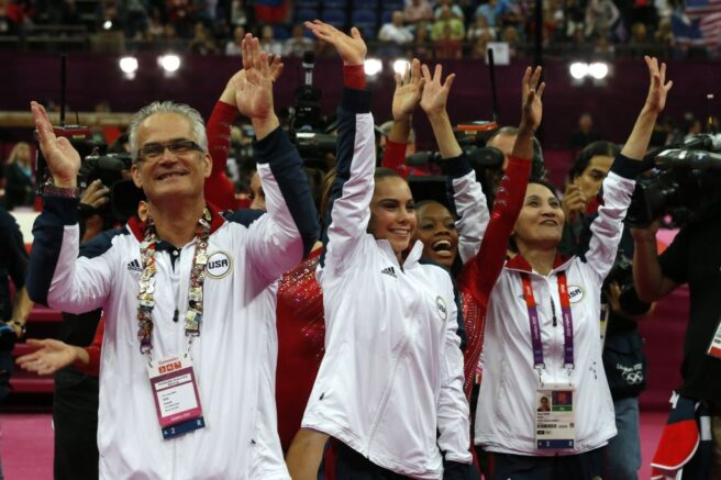 US gymnasts Gabrielle Douglas (C), Mckayla Maroney (2D-L), coaches Jenny Zhang (R) and John Geddert (L) celebrate winning gold in the women's team of the artistic gymnastics event of the London Olympic Games on July 31, 2012 at the 02 North Greenwich Arena in London. Team US won gold, Team Russia took silver and Team Romania got bronze. AFP PHOTO / THOMAS COEX / AFP PHOTO / - (Photo credit should read -/AFP via Getty Images)