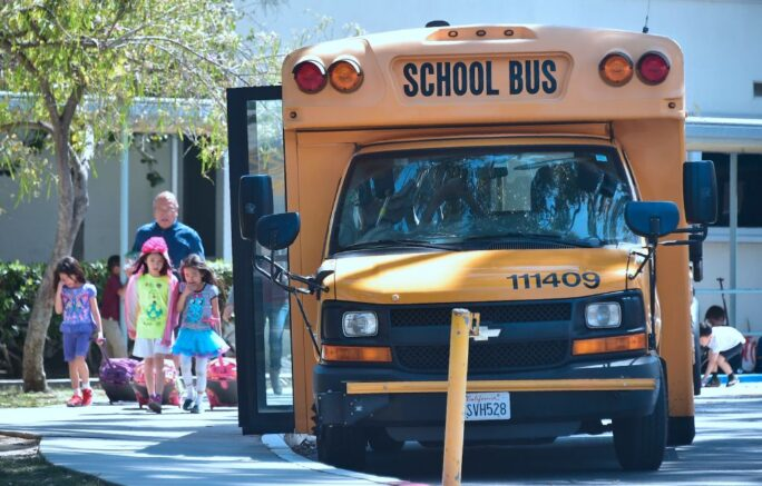 Children walk past a School Bus in Monterey Park, California on April 28, 2017. (Photo by FREDERIC J. BROWN/AFP via Getty Images)