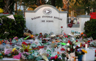 Flowers, candles and mementos sit outside one of the makeshift memorials at Marjory Stoneman Douglas High School in Parkland, Florida on February 27, 2018. Florida's Marjory Stoneman Douglas high school will reopen on February 28, 2018 two weeks after 17 people were killed in a shooting by former student, Nikolas Cruz, leaving 17 people dead and 15 injured on February 14, 2018. / AFP PHOTO / RHONA WISE (Photo credit should read RHONA WISE/AFP via Getty Images)