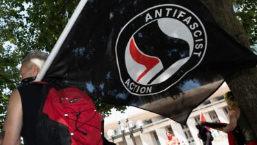 An anti-fascist protester holds a flag on the Christian Science Plaza, Saturday, July 11, 2020, in Boston. Dozens of demonstrators gathered in counter-protest against an anticipated rally by a right-wing group that never materialized. (AP Photo/Michael Dwyer)