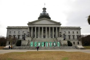 A group who opposes a bill that would ban almost all abortions in South Carolina put up a sign outside the Statehouse on Tuesday, Feb. 2, 2021, in Columbia, S.C. The bill has passed the Senate and been sent to the House. (AP Photo/Jeffrey Collins)