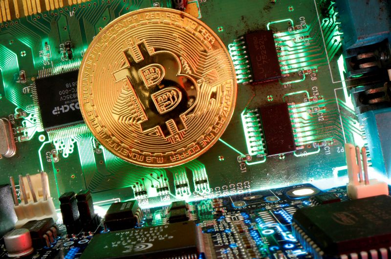 FILE PHOTO: Representation of the virtual currency Bitcoin is seen on a motherboard in this picture illustration