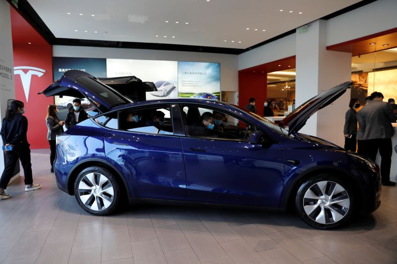 Visitors wearing face masks check a China-made Tesla Model Y sport utility vehicle (SUV) at the electric vehicle maker's showroom in Beijing