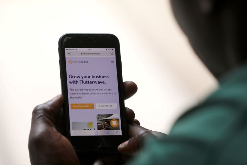 FILE PHOTO: Man poses as he displays Flutterwave homepage on mobile phone screen in Abuja