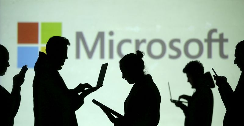 FILE PHOTO: Silhouettes of laptop and mobile device users are seen next to a screen projection of Microsoft logo in this picture illustration