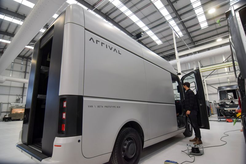 A man stands next to a fully-electric test van, due to go into production in 2022, in Banbury