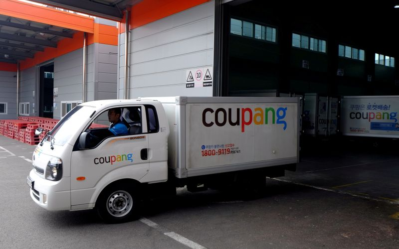 FILE PHOTO: Delivery trucks for e-commerce retailer Coupang leave a distribution centre in Seoul