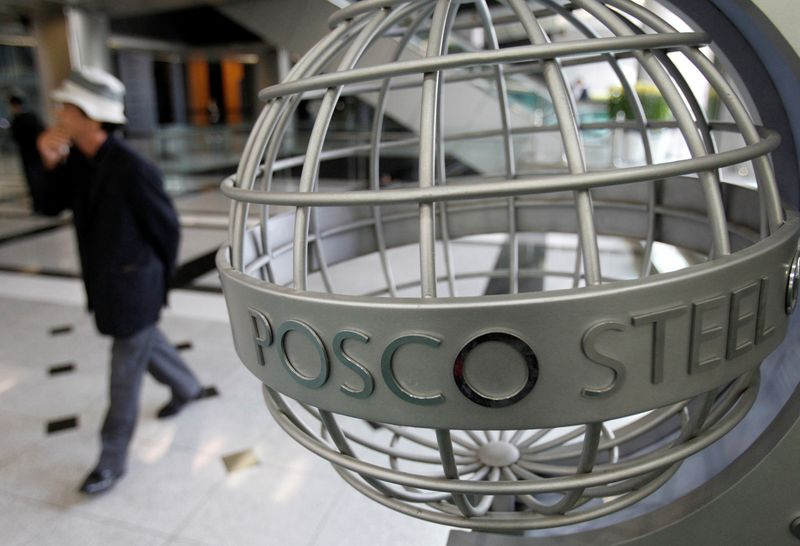 A man walks past a logo of POSCO at the company's headquarters in Seoul