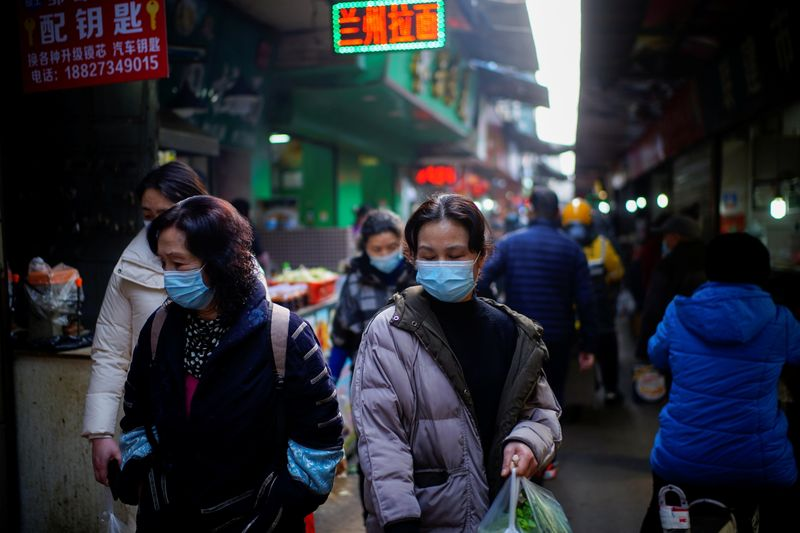 People wearing face masks walk on a street market, following an outbreak of the coronavirus disease (COVID-19) in Wuhan