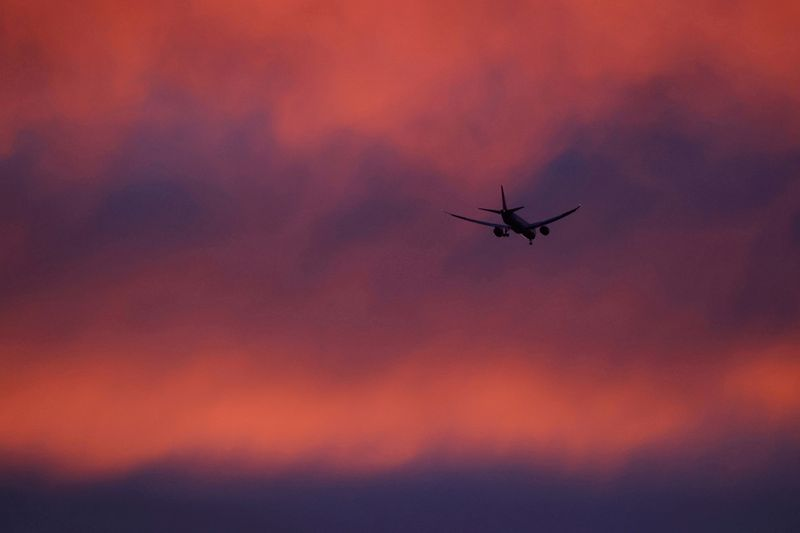 FILE PHOTO: FILE PHOTO: A plane flies in a red sky above London