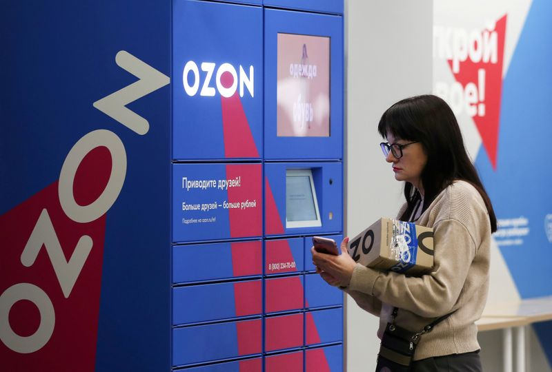 FILE PHOTO: A woman picks up an order at the pick-up point of the Ozon online retailer in Moscow, Russia