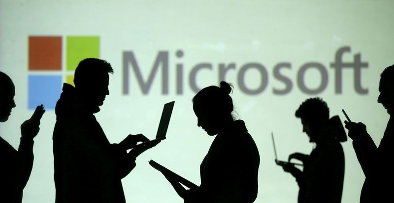 FILE PHOTO: FILE PHOTO: Silhouettes of laptop and mobile device users are seen next to a screen projection of Microsoft logo in this picture illustration