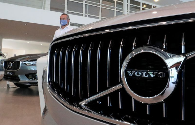 FILE PHOTO: An employee at a Volvo car dealer, wearing a protective mask is seen in the showroom, amid the coronavirus disease (COVID-19) outbreak in Brussels