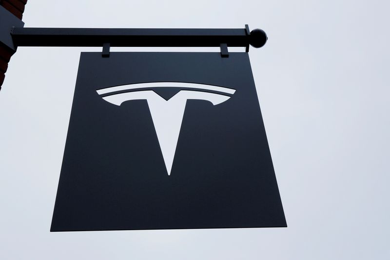 FILE PHOTO: FILE PHOTO: A Tesla logo hang on a building outside of a Tesla dealership in New York